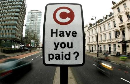 A congestion charge pay reminder sign is seen in London February 19, 2007. REUTERS/Alessia Pierdomenico (BRITAIN)