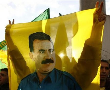 A Kurdish protester is silhouetted against a flag showing imprisoned Kurdistan Workers Party (PKK) leader Abdullah Ocalan during a rally against Turkey, in Berlin November 4, 2007. A European Union court ruled against the way the Kurdistan Workers Party (PKK) was put on the bloc's list of groups whose funds must be frozen to help fight terrorism in 2002, but the EU said the ruling was irrelevant. REUTERS/Wolfgang Rattay