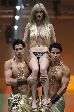 A model is carried on the shoulders of two other models as she displays a diamond-studded thong during Viva La Eve by Triumph at the Singapore Fashion Festival April 3, 2008. The thong, valued at S$168,000 ($121,106), is decorated with 518 diamonds totalling 30 carats. REUTERS/Vivek Prakash (SINGAPORE)