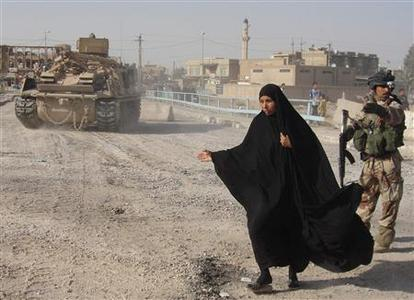 A woman walks past an Iraqi soldier standing guard as a U.S. vehicle sets concrete barriers in Baghdad's Shula district during the vehicle curfew April 2, 2008. REUTERS/Yasser Faisal