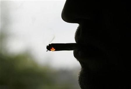 A man smokes a cigarette outside his factory in Bordeaux, southwestern France, December 15, 2006. REUTERS/Regis Duvignau