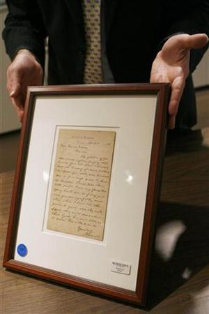 Selby Kiffer, American manuscript expert at Sotheby's, holds a letter written by Abraham Lincoln responding to children asking that he free ''all the little slave children'' that is part of a collection of historical American manuscripts to be auctioned by Sotheby's in New York March 28, 2008. REUTERS/Lucas Jackson