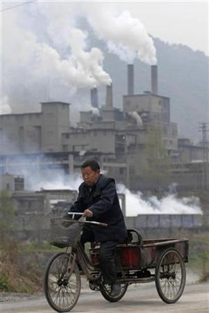 A man rides a tricycle past a cement plant in Baokang, Hubei province March 31, 2008. Developing countries and environmental groups accused the World Bank on Friday of trying to seize control of the billions of dollars of aid that will be used to tackle climate change in the next four decades. REUTERS/Stringer