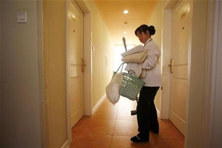 A maid leaves a room after cleaning it at the Home Inn budget hotel in Shanghai January 5, 2008. REUTERS/Nir Elias