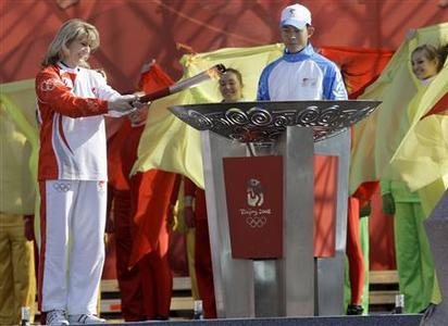 Russian speed skater and Olympic champion Svetlana Zhurova (L) lights the Olympic flame at the end of the St.Petersburg leg of the Olympic torch relay April 5, 2008. REUTERS/Alexander Demianchuk