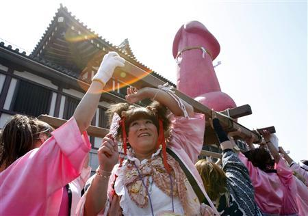 Participants dressed in women's clothes carry a portable phallic shrine during the Kanamara Festival, a fertility ritual, near Wakamiya Hachimangu Shrine in Kawasaki, south of Tokyo April 6, 2008. REUTERS/Issei Kato