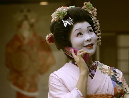 Geisha Anzu uses her mobile phone after finishing a banquet at a traditional Japanese restaurant in Tokyo November 5, 2007. REUTERS/Toru Hanai/Files