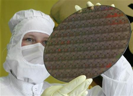 An AMD technician displays a wafer for the media in Dresden, Germany, May 17, 2004. REUTERS/Arnd Wiegmann