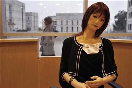 A woman walks by a Japanese-made robot receptionist at Ben-Gurion University in Israel, February 5, 2007. Robots could fill the jobs of 3.5 million people in greying Japan by 2025, a thinktank says, helping to avert worker shortages as the country's population shrinks. REUTERS/Gil Cohen Magen