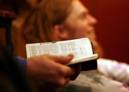 A man holds a bible during church services in the Brooklyn borough of New York, February 18, 2007. REUTERS/Shannon Stapleton
