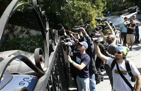 Media crews and the paparazzi rush to the gate at hotel heiress Paris Hilton's home in the West Hollywood area of Los Angeles June 7, 2007. REUTERS/Gus Ruelas