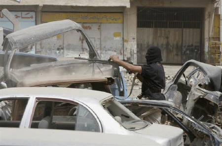 A hooded Mehdi army fighter fires his machinegun during clashes against Iraqi and U.S. soldiers in Baghdad's Sadr City April 8, 2008. REUTERS/Kareem Raheem