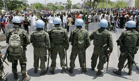 U.N. peacekeepers stand guard while residents protest food prices on the streets in Port-au-Prince April 8, 2008. REUTERS/Eduardo Munoz
