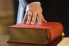 <p>La Bibbia sotto la mano di un arcivescovo tedesco. REUTERS/Michael Dalder</p>