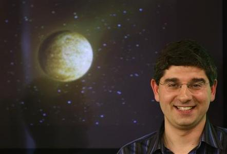 Spain's scientist Ignasi Ribas smiles as he poses beside a simulated picture of the smallest planet ever discovered outside our solar system during a news conference at Spain's Superior Council for Scientific Investigations (CSIC) in Madrid April 9, 2008. The rocky planet, known as GJ 436c and with a radius about 50 percent greater than the Earth's, has been found by Spanish scientists who believe they will detect Earth-like planets potentially able to harbour life within a few years. REUTERS/Sergio Perez