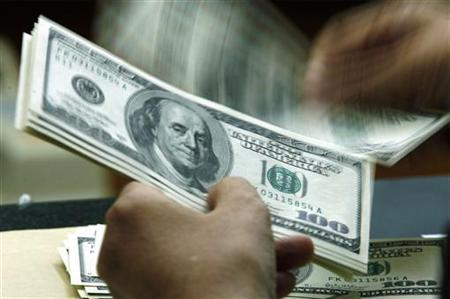 A customer counts hundred dollar bills in a file photo. REUTERS/Beawiharta