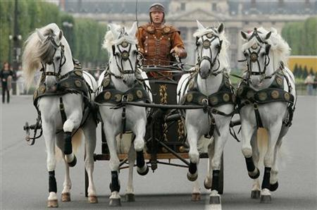Stunt expert and horse trainer Mario Luraschi rides in chariot as he crosses the Pont d'Iena near the Eiffel Tower during a parade to promote a production of 'Ben Hur' in Paris August 27, 2006. REUTERS/Benoit Tessier