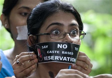 A medical student reacts as a fellow student fixes a ''no reservation'' band before the start of a silent march during a protest against the reservation of college places for lower castes, in the eastern Indian city of Kolkata August 25, 2006. India's Supreme Court upheld on Thursday a government policy to reserve more college seats for students from lower castes, a fiercely debated affirmative action scheme intended to help flatten centuries-old social hierarchies. REUTERS/Parth Sanyal