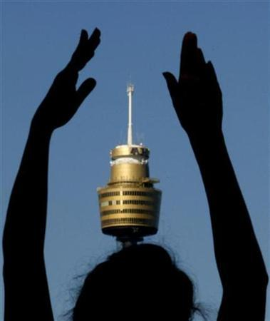 A yoga enthusiast performs sun salutations in front of the Centrepoint tower in Sydney October 10, 2007. REUTERS/Tim Wimborne