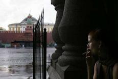 <p>Женщина курит во время проливного дождя в центре Москвы 7 августа 2007 года. Госдума единодушно ратифицировала рамочную конвенцию ВОЗ по борьбе с табаком, которая предусматривает постепенный запрет на рекламу табачных изделий, ограничение курения в общественных местах и повышение цен на табачные изделия. (REUTERS/Denis Sinyakov)</p>