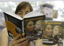 <p>Женщина читает книгу Анжелы Ермаковой в одном из книжных магазинов Москвы 16 августа 2007 года. Банк России предлагает закрепить русский язык в странах ЕврАзЭС и использовать его как конкурентное преимущество в борьбе за международный финансовый центр между Москвой и Лондоном. (REUTERS/Stringer)</p>