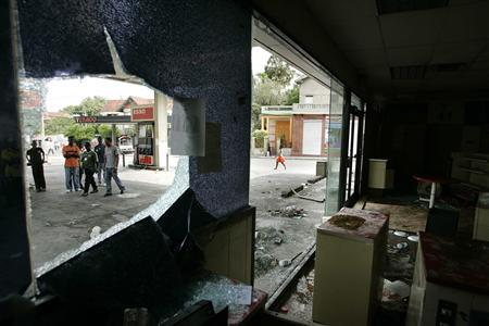 Haitians look at the damages caused by looters at a gas station in Port-au-Prince April 10, 2008. REUTERS/Eduardo Munoz