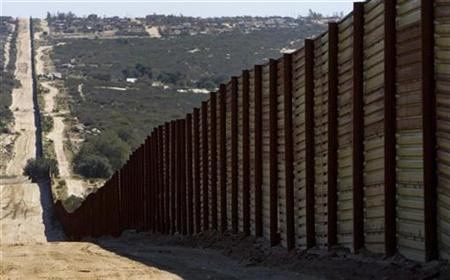 The metal border fence stretches across a valley separating the US and Mexico, near Campo, California on March 17, 2008. REUTERS/Fred Greaves