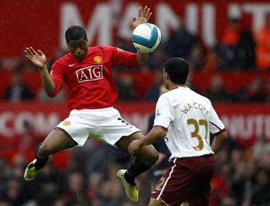 Manchester United's Patrice Evra (L) challenges Arsenal's Theo Walcott for the ball during their English Premier League football match at Old Trafford in Manchester, April 13, 2008. REUTERS/Darren Staples. NO ONLINE/INTERNET USAGE WITHOUT A LICENCE FROM THE FOOTBALL DATA CO LTD. FOR LICENCE ENQUIRIES PLEASE TELEPHONE ++44 (0) 207 864 9000.