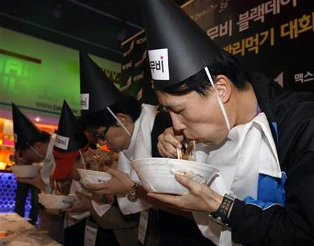 Participants eat Jajangmyeon, Chinese-style noodles topped with a thick sauce of black bean paste, at a speed eating competition, sponsored by an online company, for movie tickets at a movie theatre in Seoul April 14, 2008. It was a Black Day for love in South Korea on Monday with lonely hearts trying to ease their pain by diving head first into bowls of noodles. Black Day is marked by people who have not found love. They dress in dark colours and commiserating over meals of black food, with the dish of choice being Jajangmyeon. REUTERS/Lee Jae-Won
