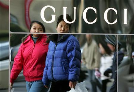 Chinese shoppers look at a Gucci store in Shanghai January 21, 2005. Luxury goods maker Gucci has won a trademark copycat lawsuit against a Chinese shoemaker, putting its foot down in a country where knock-off designer gear is on sale on every street corner, state media said on Tuesday. REUTERS/Claro Cortes