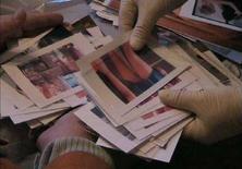 <p>Funzionari dell'Ufficio anticrimine regionale di Magdeburg, in Germania, controllano tra le fotografie di un uomo sospettato di aver ordinato immagini pedopornografiche tramite Internet. REUTERS/Handout/LKA Sachsen-Anhalt/Akte07 (GERMANY)</p>
