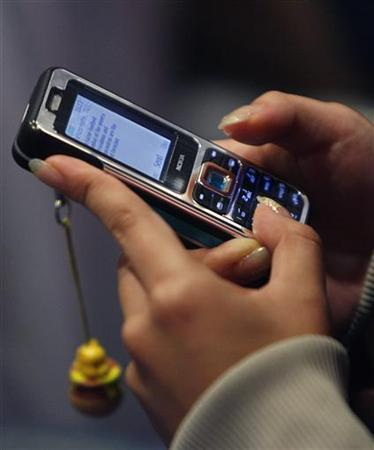 A competitor types a text message into a mobile phone during a competition in Singapore November 12, 2006. Jaxtr, a Silicon Valley startup that lets users bypass a carrier's international phone charges via the Web, said on Wednesday it is offering free mobile phone text messages between 38 countries. REUTERS/Vivek Prakash