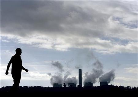 A man walks past the Ratcliffe-on-Soar power station in central England, central England, October 30, 2006. Climate change expert Nicholas Stern says he under-estimated the threat from global warming in a major report 18 months ago when he compared the economic risk to the Great Depression of the 1930s. REUTERS/Darren Staples