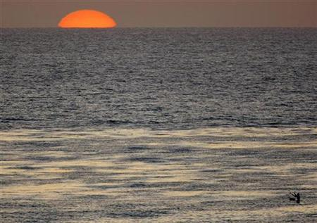 The sun sets as a fisherman casts his line in the Pacific Ocean while sitting on a surfboard off the coast of Cardiff, California April 1, 2008. REUTERS/Mike Blake