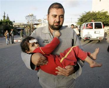 A man carries a wounded Palestinian girl after witnesses said she was injured from an Israeli air strike in the central Gaza Strip April 16, 2008. REUTERS/Ibraheem Abu Mustafa