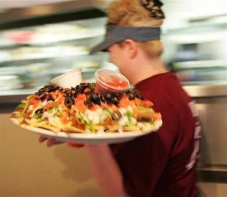 A waitress serves nachos in a file photo. High cholesterol levels in your 40s may raise the chance of developing Alzheimer's disease decades later, according to a study underscoring the importance of health factors in middle age on risk for the brain ailment. REUTERS/Molly Riley