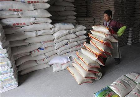 A worker pushes a cart loaded with packs of rice at a storage house in Hefei, Anhui province April 16, 2008. REUTERS/Jianan Yu
