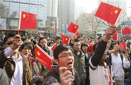 Locals hold Chinese national flags as they shout slogans outside a Carrefour supermarket in Qingdao, Shandong province April 18, 2008. .REUTERS/Stringer
