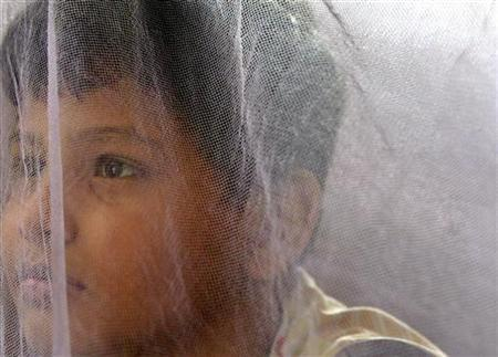 A boy sits inside a mosquito net at home after being discharged from a hospital in Kolkata in a file photo. The British entrepreneur who sold a football Web site at the age of 17 for $40 million (20 million pounds) has switched his attention to help launch a social networking site on Sunday designed to fight malaria. REUTERS/Parth Sanyal