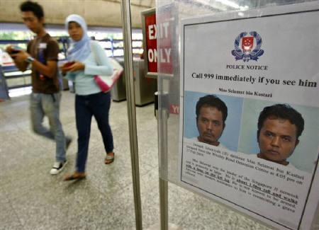 Commuters walk past a poster of suspected Islamic militant Mas Selamat bin Kastari at an MRT train station in Singapore April 21, 2008. REUTERS/Vivek Prakash