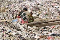 <p>Ребенок со своими родителями питаются на свалке в Джакарте 25 марта 2008 года. Рост цен на продовольствие мешает попыткам сократить мировой уровень нищеты, экономическому росту и безопасности, сказал генеральный секретарь ООН Пан Ги Мун в воскресенье. (REUTERS/Beawiharta)</p>