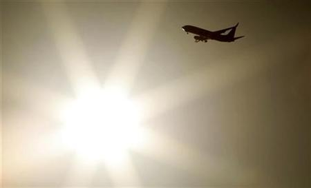 A passenger jet passes in front of the sun as it approaches Sydney airport April 11, 2008. After a spate of incidents of pilots being disoriented and often having to change course when their aircraft have been targeted with laser pointers, New South Wales state is considering a ban on the pointers, local media have reported. REUTERS/Tim Wimborne