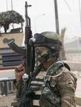 <p>Военнослужащий иракской армии охраняет дорогу в городе Басра 19 апреля 2008 года. Правительство Ирака будет противостоять вооруженным формированиям в стране, чтобы не допустить начала всеобщей войны, как угрожает духовный лидер шиитов Ирака Моктада аль-Садр, заявил министр иностранных дел страны Хошнияр Зебари. (REUTERS/Atef Hassan)</p>