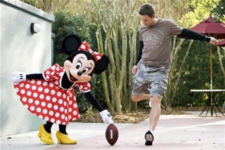 NFL football New York Giants kicker Lawrence Tynes gets some help from Minnie Mouse during a kicking demonstration at Disney's Hollywood Studios in Lake Buena Vista, Florida, February 29, 2008. REUTERS/Matt Stroshane/Handout