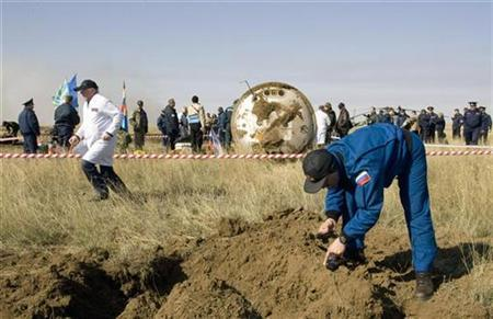 A ground crew member checks radiation levels near the Soyuz capsule after it landed in northern Kazakhstan April 19, 2008. REUTERS/Shamil Zhumatov