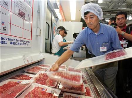 A store clerk adjusts packed U.S. beef at Costco Japan supermarket in Chiba, east of Tokyo August 9, 2006. REUTERS/Yuriko Nakao