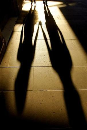 A young couple walking hand-in-hand cast a late afternoon shadow on a city street December 29, 2007. REUTERS/Tim Wimborne