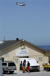 Lifeguards stand by a covered van parked at their station in Solana Beach, California April 25, 2008 as a Coast Guard helicopter searches for a shark in the waters off the coast after a man was involved in a fatal shark attack. REUTERS/Mike Blake