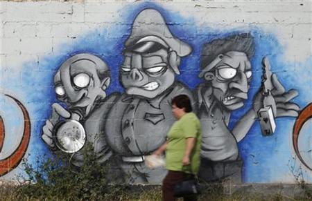A woman walks past a mural depicting (L-R) a drug addict, a police officer and a car thief in the border city of Tijuana, in this April 18, 2007 file photo. REUTERS/Tomas Bravo/Files