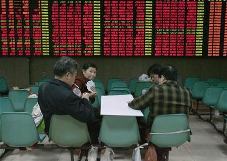 Investors play cards in front of an electronic board showing stock information at a brokerage house in Nanjing, Jiangsu province April 21, 2008. REUTERS/Sean Yong